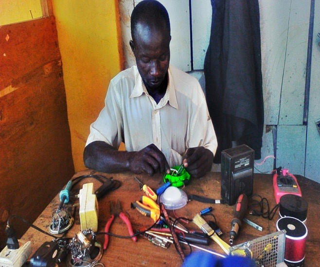 Robert repairing a solar light at his workshop in Gulu Town
