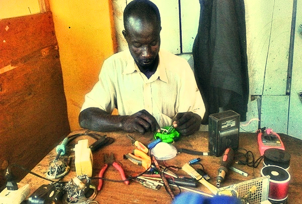 Akera Robert mending a solar light 4