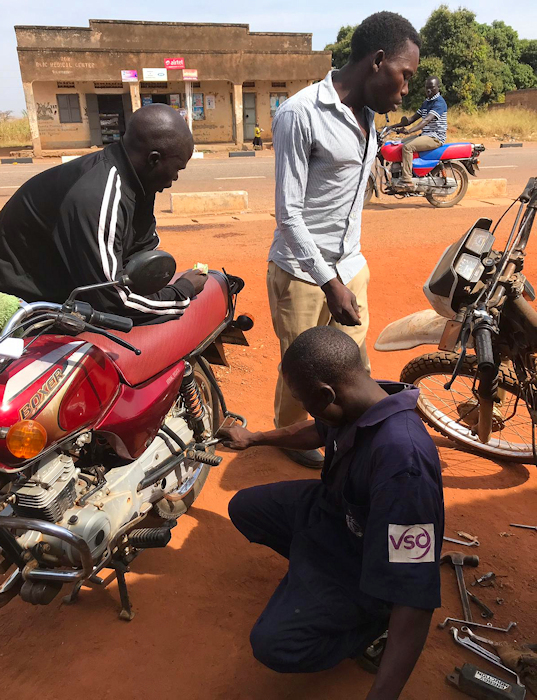 Jokene from Tam Anyim working on a Bajaj Boxer and Yahama 125 at the same time